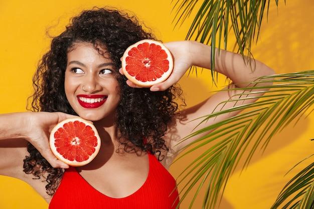 Portret pięknej uśmiechniętej młodej kobiety w bikini stojącej na tle żółtej egzotycznej ściany, pozującej z przepołowionym grejpfrutem