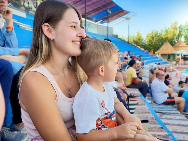 Portret pięknej uśmiechniętej młodej kobiety z małym synkiem siedzącej na trybunach areny i czekającej na przedstawienie