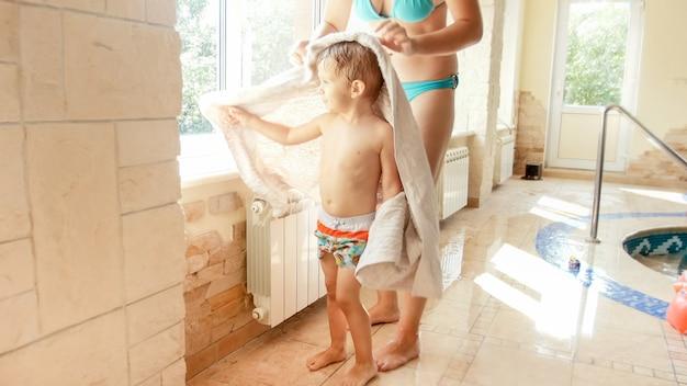Portret pięknej uśmiechniętej młodej kobiety zakrywającej i wycierającej swojego 3-letniego synka po kąpieli w krytym basenie