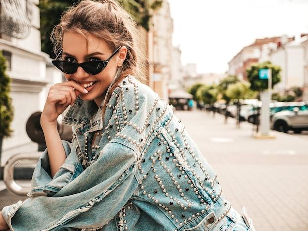 Portret pięknej uśmiechniętej modelki ubranej w letnią kurtkę jeansową hipster
