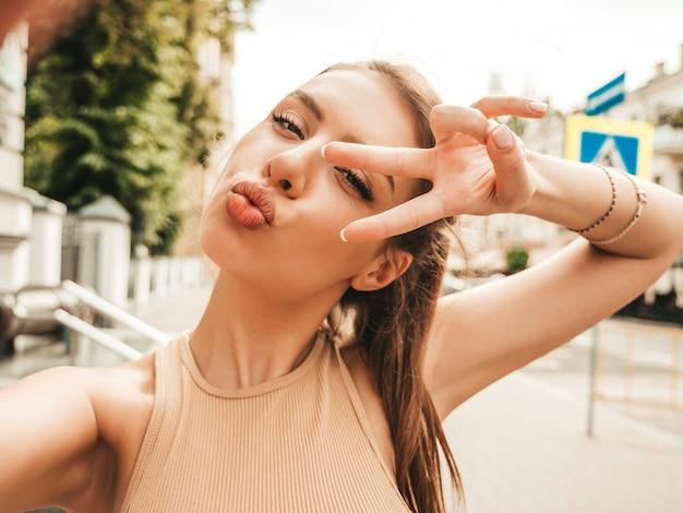 Portret pięknej uśmiechniętej modelki ubranej w letnie spodenki jeansowe hipster