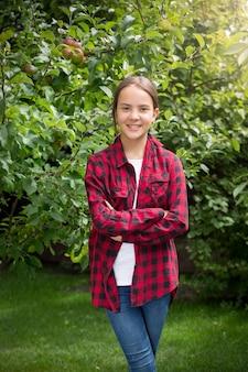 Portret pięknej uśmiechniętej nastoletniej dziewczyny pozuje w ogrodzie