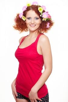 Portret pięknej uśmiechniętej rudzielec imbirowa kobieta w czerwonym płótnie z kolor żółty różowymi kolorowymi kwiatami w włosy odizolowywającym na bielu