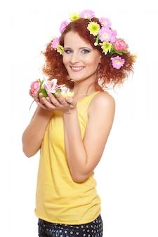 Portret pięknej uśmiechniętej rudzielec imbirowa kobieta w żółtym płótnie z kolor żółty różowymi kolorowymi kwiatami w włosy odizolowywającym na białym mieniu kwitnie
