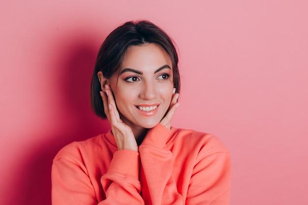 Portret pięknej uśmiechniętej uroczej brunetki kobiety w ubranie na co dzień sweter brzoskwiniowy z jasnym makijażem i różowe usta na białym tle