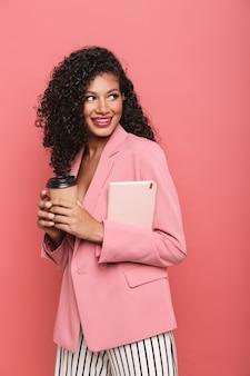 Portret pięknej, uśmiechniętej, uroczej młodej kobiety w letnim ubraniu, stojącej na białym tle nad różową ścianą, trzymającej filiżankę kawy na wynos i pamiętnik