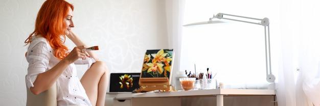 Portret pięknej utalentowanej artystki siedzącej na krześle i tworzącej kwiatowe zdjęcie.