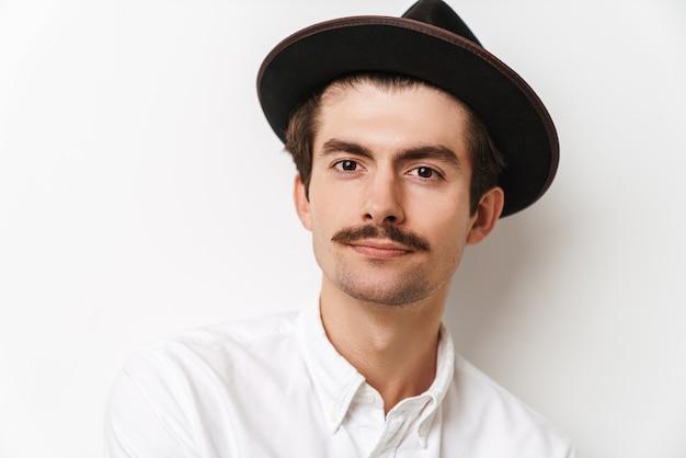 Portret pięknej wąsaty mężczyzna na sobie kapelusz i koszulę, patrząc z przodu na białym tle