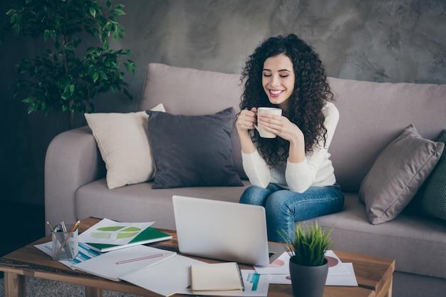 Portret pięknej wesołej dziewczyny siedzącej na kanapie, pijąc kawę, oglądając wideo online w nowoczesnym loftowym stylu industrialnym wnętrzu salonu w pomieszczeniu