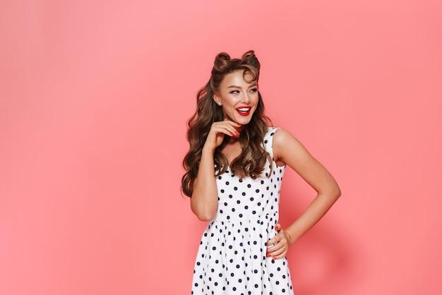 Portret pięknej wesołej młodej dziewczyny pin-up na sobie sukienkę stojącą na białym tle, pozowanie