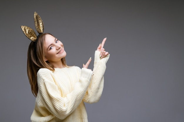 Portret pięknej wesołej młodej kobiety w swetrze i uszach króliczka pokazuje palcem z boku