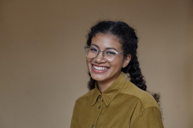 Portret pięknej wesołej młodej kręconej kobiety o ciemnej skórze w okularach podczas pozowania, szczęśliwie patrząc z czarującym szerokim uśmiechem
