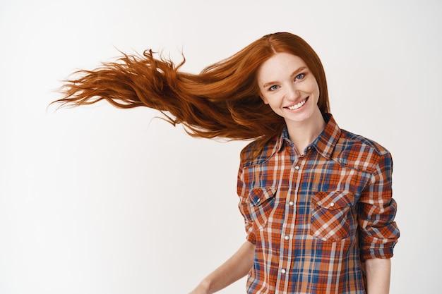 Portret pięknej wesołej rudej kobiety z latającymi kręconymi włosami uśmiecha się śmiejąc się patrząc na przód nad białą ścianą