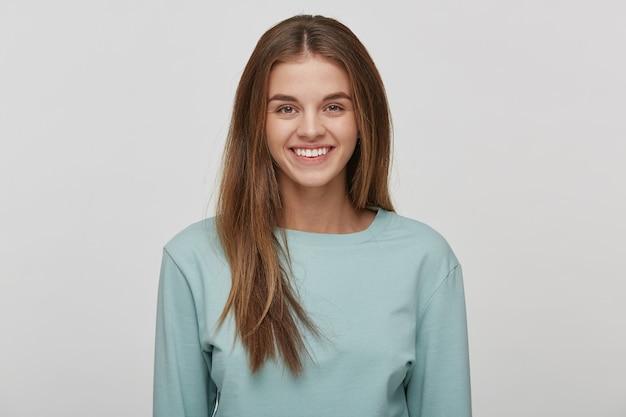 Portret pięknej wesołej szczęśliwej młodej kobiety z naturalnym makijażem i zadbanymi włosami, uśmiecha się