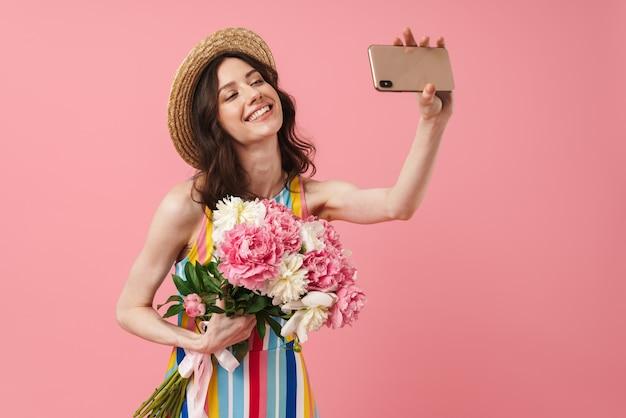 Portret pięknej, wesołej uśmiechniętej młodej uroczej kobiety pozującej na białym tle nad różową ścianą trzymającą kwiaty weź selfie przez telefon komórkowy