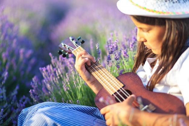 Portret pięknej wiejskiej dziewczyny o brązowych włosach, która uczy się grać na ukulele w pięknym miejscu wśród kwiatu lawendy