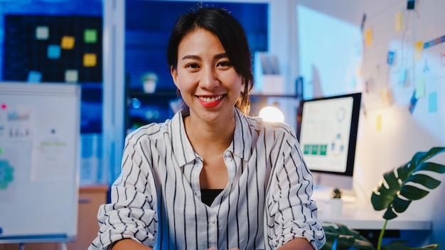 Portret pięknej wykonawczej bizneswoman smart casual patrząc na kamery i uśmiechnięty, szczęśliwy w nocy nowoczesnego biura pracy.