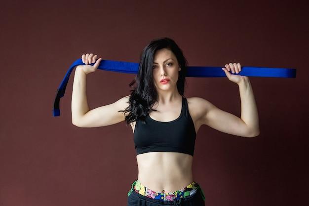 Portret pięknej wysportowanej kobiety z niebieskim paskiem na tle ściany koncepcja sztuk walki