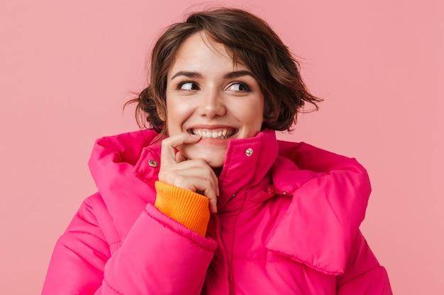 Portret pięknej zadowolonej kobiety w ciepłym płaszczu, uśmiechniętej i patrzącej na bok, odizolowanej na różowo