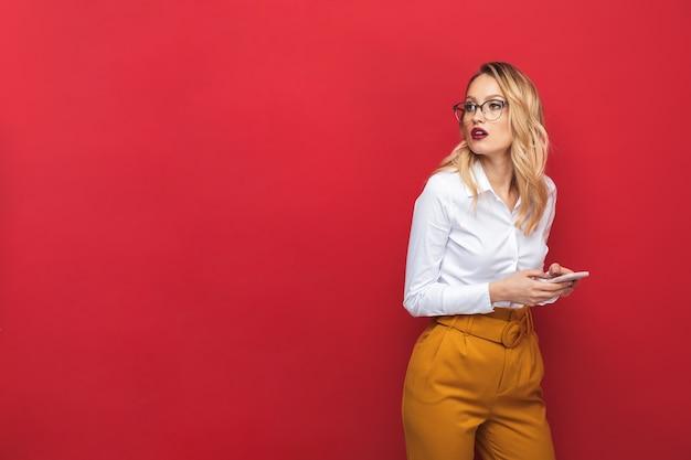 Portret pięknej zamyślonej młodej kobiety blondynka stojącej na białym tle na czerwonym tle, trzymając telefon komórkowy