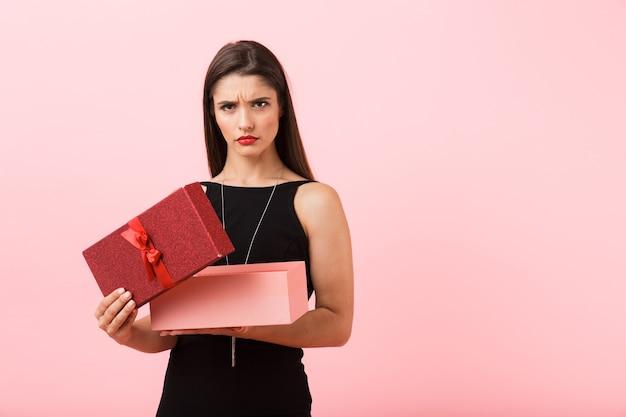 Portret pięknej zdenerwowanej młodej kobiety na sobie czarną sukienkę stojącej na białym tle na różowym tle, otwórz pudełko