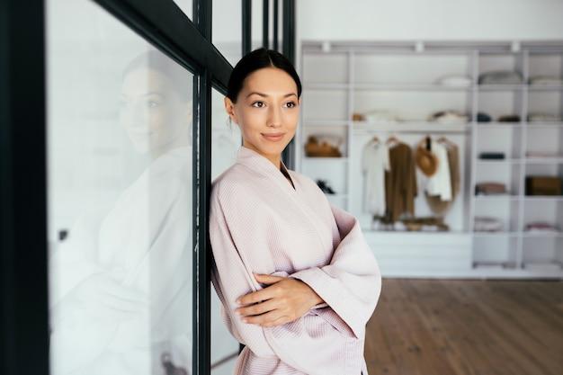 Portret pięknej zdrowej kobiety w szlafroku pozowanie na kamery w pomieszczeniu
