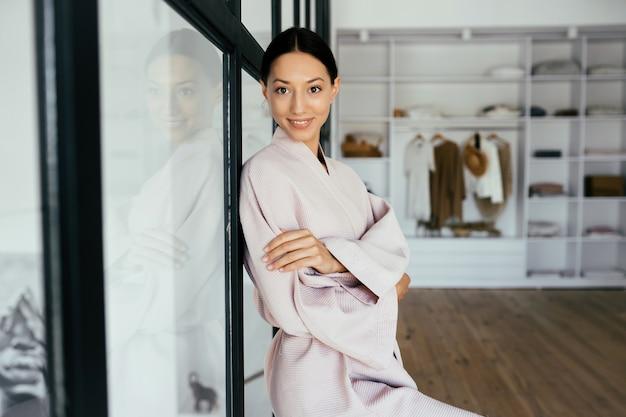 Portret pięknej zdrowej kobiety w szlafroku pozowanie w pomieszczeniu