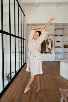 Portret pięknej zdrowej kobiety w szlafroku pozuje do kamery w pomieszczeniu