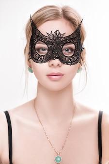 Portret pięknej zmysłowej blond kobiety z zielonymi oczami w czarnej koronkowej masce na jasnym tle. maska wenecka