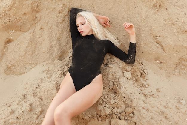 Portret pięknej zmysłowej blondynki w czarnym body leży na piasku.