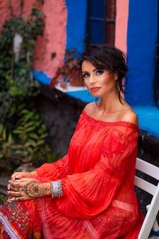Portret pięknej, zmysłowej eleganckiej brunetki, z makijażem i modnym czerwonym strojem. styl cygański.