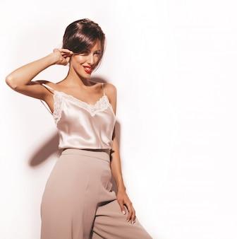 Portret pięknej zmysłowej kobiety brunetka. dziewczyna w eleganckich beżowych klasycznych ubraniach i szerokich spodniach. model na białym tle