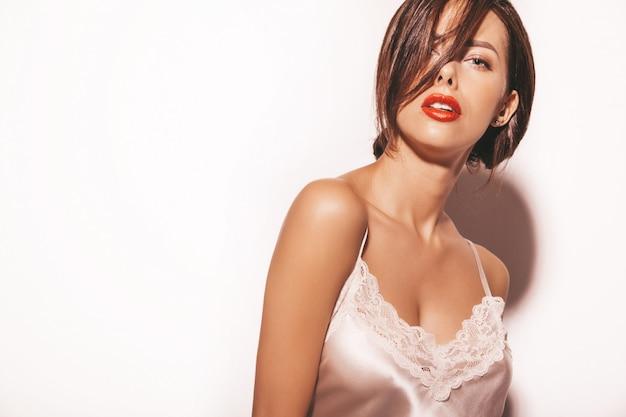 Portret pięknej zmysłowej kobiety brunetka. dziewczyna w eleganckich beżowych klasycznych ubraniach. modeluje z czerwonymi wargami odizolowywać na bielu