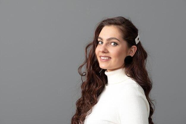 Portret pięknej zmysłowej kobiety z długimi kręconymi włosami na białym tle na szarym tle