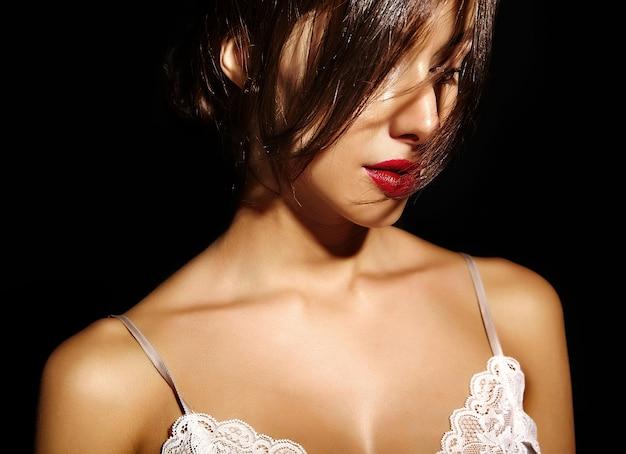 Portret pięknej zmysłowej ślicznej seksownej brunetki kobiety z czerwonymi wargami w piżamy bieliźnie na czarnym tle. z włosami zakrywającymi włosy