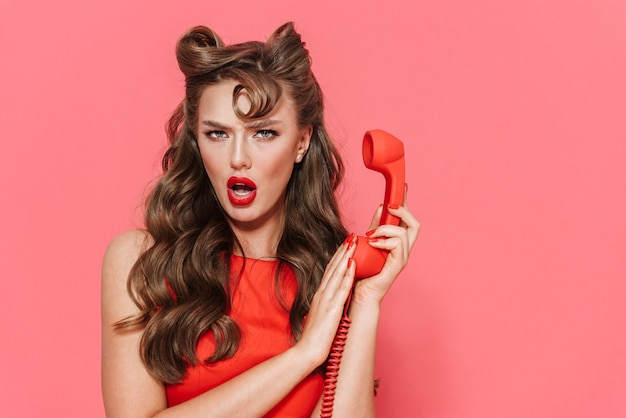 Portret pięknej zszokowanej młodej dziewczyny pin-up na sobie sukienkę stojącą na białym tle, rozmawia przez telefon stacjonarny