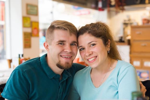 Portret piękni potomstwa dobiera się w miłości przy sklep z kawą.