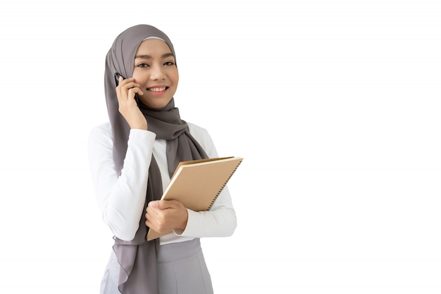 Portret piękny azjatycki muzułmański uczeń trzyma książkę i pencile, muzułmański studencki główkowanie