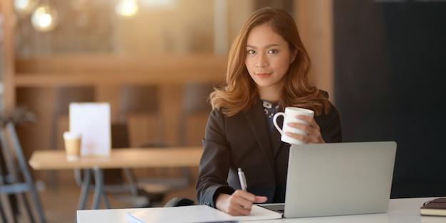 Portret piękny azjatykci bizneswoman pracuje na jej projekcie z laptopem i pije kawę