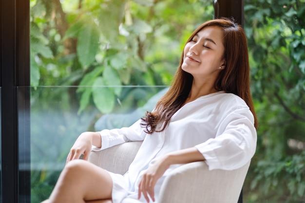 Portret piękny azjatykci kobiety obsiadanie na białym karle z zieloną naturą