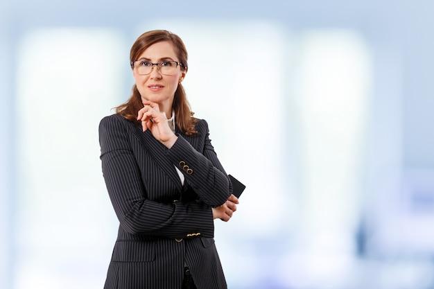 Portret piękny bizneswomanu 50 ucho starego z telefonem komórkowym w biurze.