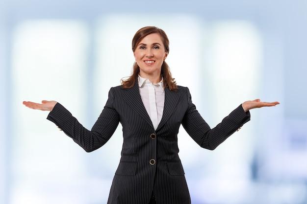 Portret piękny bizneswomanu 50 ucho starych w szeroko otwartej ręki pozie odizolowywającej na bielu.