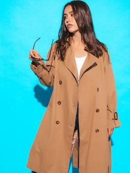 Portret piękny caucasian brunetki kobiety model w brown płaszczu i okularach przeciwsłonecznych dziewczyna pozuje blisko błękit ściany