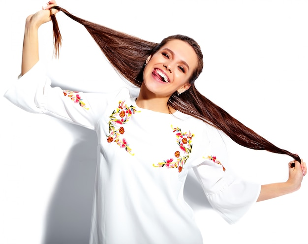 Portret piękny caucasian uśmiechnięty brunetki kobiety model w białego lata eleganckiej sukni odizolowywającej na białym tle. skręcone włosy