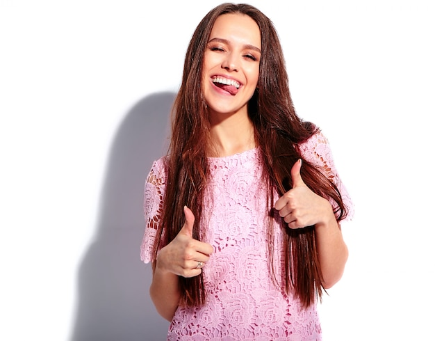 Portret piękny caucasian uśmiechnięty brunetki kobiety model w jaskrawej różowej lato eleganckiej sukni odizolowywającej na białym tle. pokazuje język, kciuki do góry
