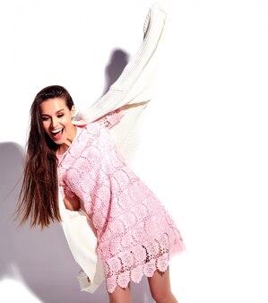 Portret piękny caucasian uśmiechnięty brunetki kobiety model w jaskrawej różowej lato eleganckiej sukni odizolowywającej na białym tle. świętowanie