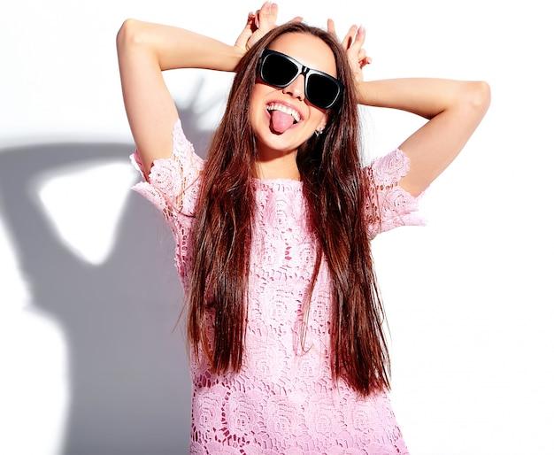 Portret piękny caucasian uśmiechnięty brunetki kobiety model w jaskrawej różowej lato eleganckiej sukni w okularach przeciwsłonecznych odizolowywających na białym tle. pokazując jej język