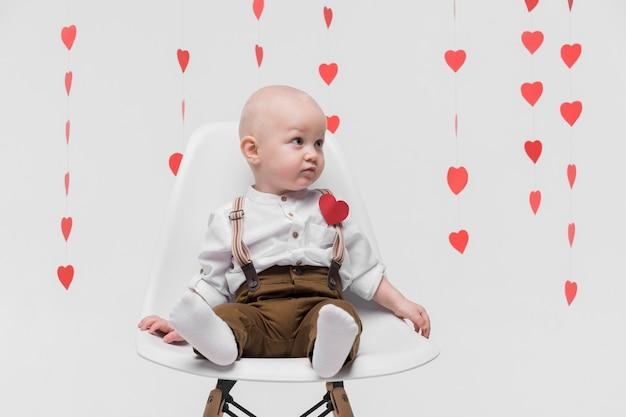 Portret piękny chłopiec siedzi na krześle