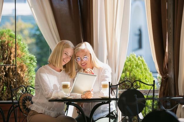 Portret piękny dorośleć matki i jej córki trzyma filiżankę siedzi w domu