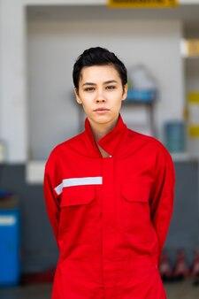 Portret piękny kaukaski kobieta mechanik ubrany w czerwony mundur pracujący nad konserwacją samochodów i serwis samochodowy